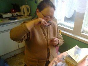Fieldwork partner Ulyana Prokopievna Koloddeznikova investigating old photographs from the glorious and sad past at Bykov Mys